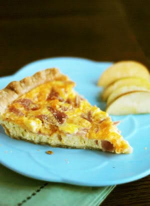 a slice of egg quiche on a blue plate with apple slices beside it