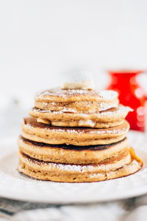 white plate and white background with a stack of pumpkin pancakes