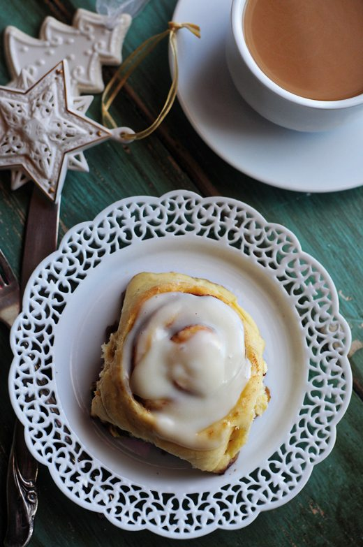 A homemade cinnamon roll on a white plate with Christmas ornaments and tea