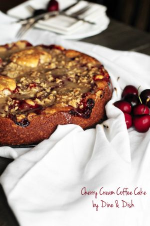 Image is of a coffee cake with cherries on a white cloth background