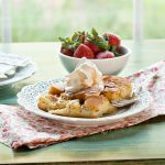 French Toast Casserole on a white plate with a colorful napkin. There's a bowl of strawberries in the background.