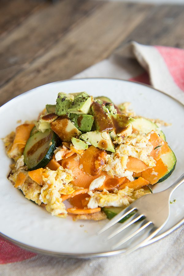 Avocado and Spiralized Sweet Potato Hash with Zucchini on a white plate with linen napkin.