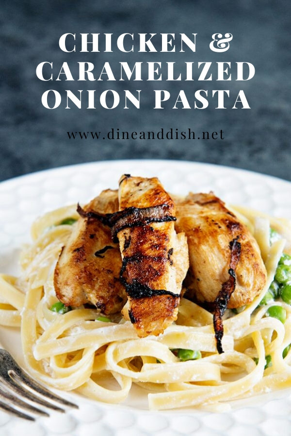 white plate with chicken, pasta and caramelized onions on grey backdrop