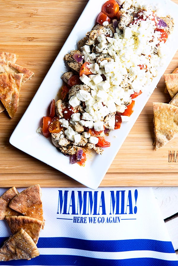 Greek Feta Chicken Appetizer Recipe served with pita chips on a Mamma Mia towel and cutting board