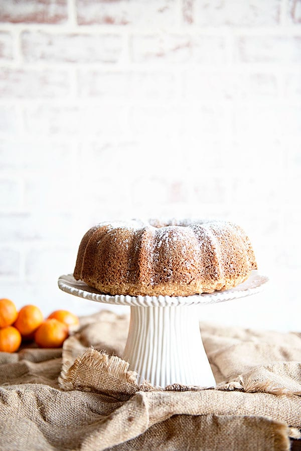 Bright white brick background with oranges and a bundt cake on a white cake stand