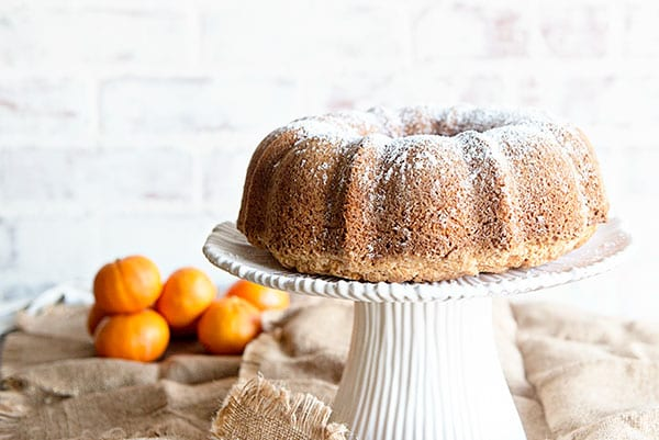 White background with an orange juice bundt cake on a white cake stand. Oranges are in the background on a burlap cloth.