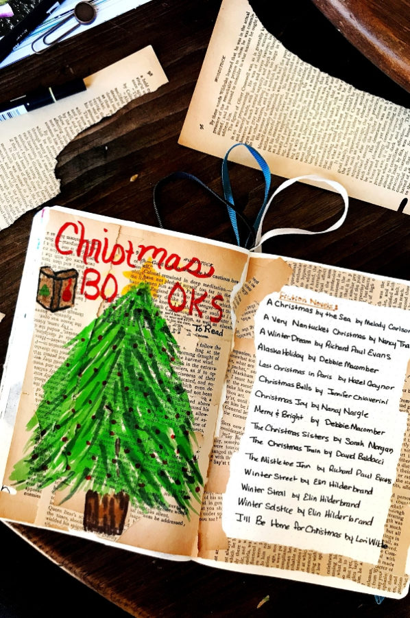 An open notebook with a Christmas tree drawing and a bullet journal spread of Christmas Books to read