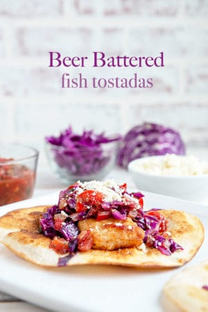 White background with a tostada featuring beer battered fish, cojita cheese and purple cabbage