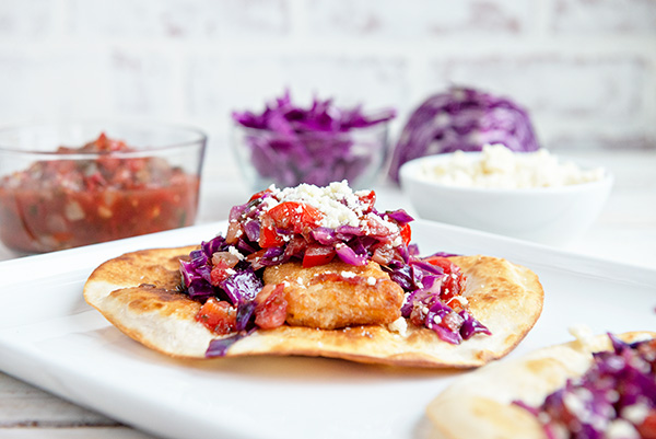 horizontal image of beer battered fish tostadas with purple cabbage on a white background