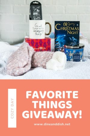 A group of cozy day necessities including socks, coffee mug, book, candle and bookmark