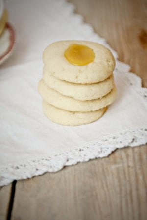 Lemon Curd Thumbprint Cookies on a cream background