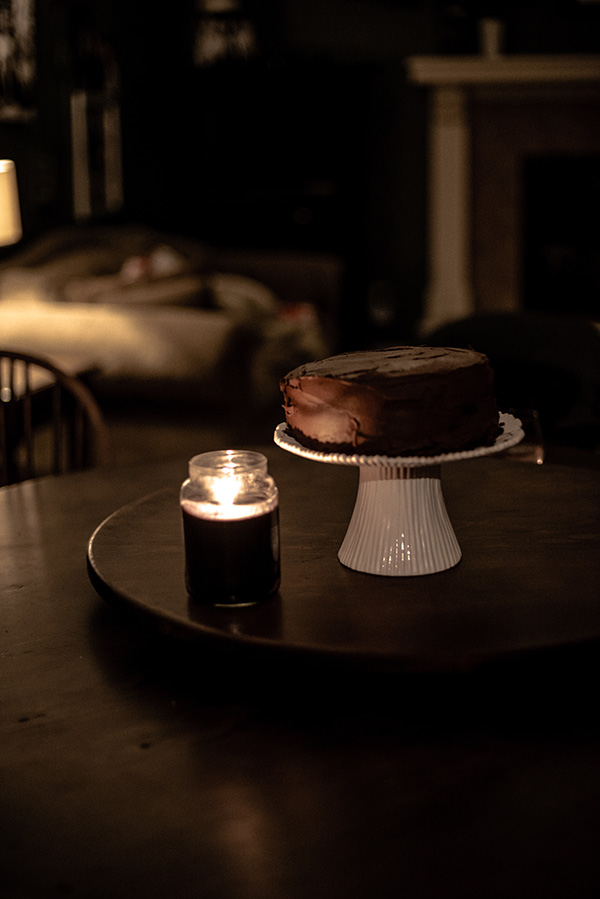 Dark Chocolate Cake on a white cake stand and wood table