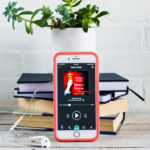 iPhone screen with Mercy House Audiobook on it, a stack of books and a green leaf plant