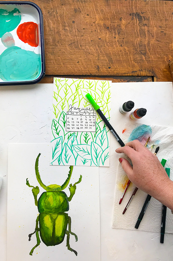 desk with a watercolor painting of a green bug