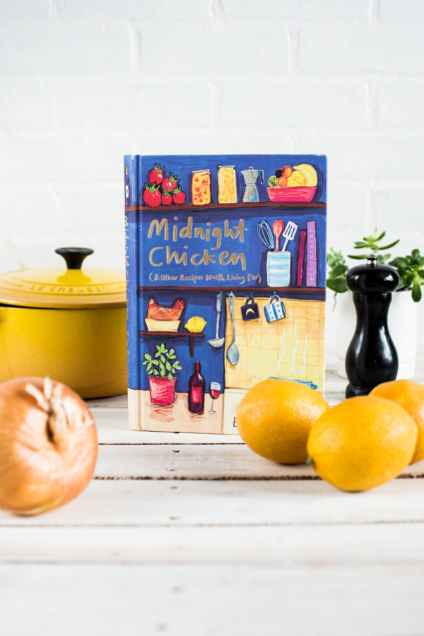 Yellow lemons and Midnight Chicken Cookbook on a white background