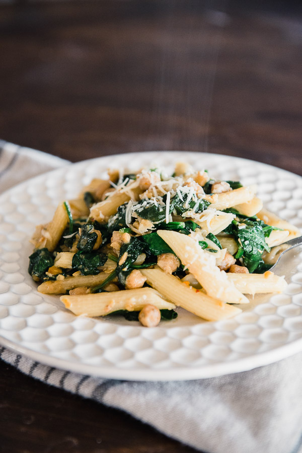 White plate with penne pasta, chickpeas, spinach and parmesan cheese