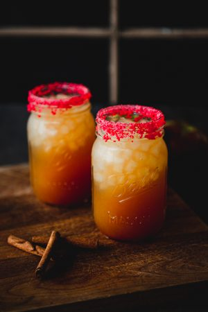 Image is of 2 mason jars on a wood background filler with a fireball cider cocktail